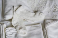 Set of white baby clothes. White set of baby clothes with socks royalty free stock images
