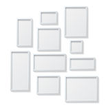 Set of White Blank Picture Frames, hanging on a White Wall from Royalty Free Stock Photos
