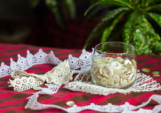 Set of white buttons in a glass. Assorted buttons white and beige tones in a glass and vintage lace on table Stock Photography