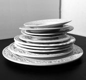 Set of white ceramic dinner relief plates on black background Royalty Free Stock Photography