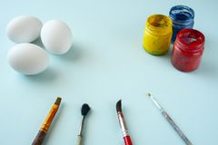 A set of white clean eggs, blue, yellow and red paints and brushes on bright background. Easter symbols. Easter eggs, painting eggs, easter illustration image stock images