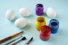 A set of white clean eggs, blue, yellow and red paints and brushes on bright background. Easter symbols. Easter eggs, painting eggs, easter illustration image royalty free stock photography