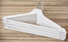 Set of white coat hangers on the wooden background Stock Photos