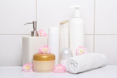 Set of white cosmetic bottles with flowers over tiled wall Royalty Free Stock Image