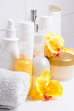 Set of white cosmetic bottles with flowers over tiled wall Royalty Free Stock Photography