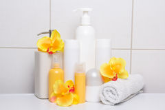 Set of white cosmetic bottles with orange flowers over tiled wal Royalty Free Stock Images