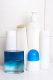 Set of white cosmetic bottles over tiled wall Royalty Free Stock Photo