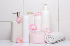 Set of white cosmetic bottles with pink flowers over tiled wall Royalty Free Stock Photos