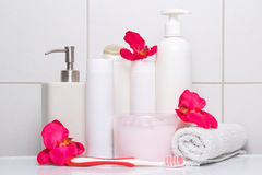 Set of white cosmetic bottles with red flowers over tiled wall Royalty Free Stock Photography