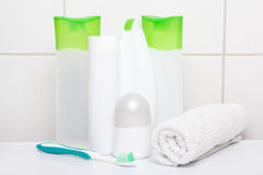 Set of white cosmetic bottles with towel and toothbrush over til Royalty Free Stock Photography