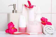 Set of white cosmetic bottles, towel and toothbrush with red flo Royalty Free Stock Photo