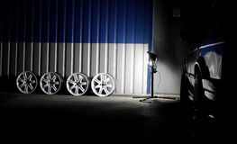 Set of white custom sportcar wheels in car workshop at night stock photos Stock Images