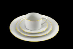 Set of white dinnerware with gold trim stock photography