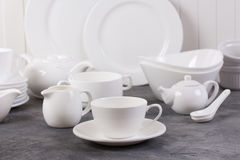 Set of white dishes on grey background Royalty Free Stock Photo