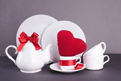 Set of white dishes for lunch and tea with decor elements from red hearts and satin ribbons on a gray background, copy space. Royalty Free Stock Photos
