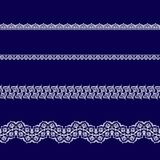 Set of white lace ribbons. On a blue background Royalty Free Stock Photography