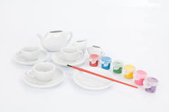 Set of white mugs with paints and paintbrush to decorate Stock Photography
