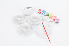 Set of white mugs with paints and paintbrush to decorate Stock Image