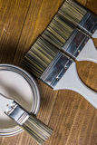 A set of white paint brushes, a metal can with white paint on a wooden texture table Royalty Free Stock Photography