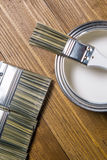 A set of white paint brushes, a metal can with white paint on a wooden texture table Stock Photography