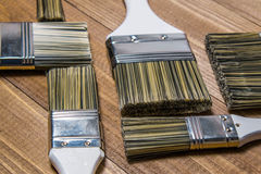 A set of white paint brushes, a metal can with white paint on a wooden texture table Stock Photo