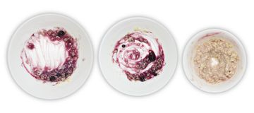A set of white plates with porridge and blueberry jam leftovers  on white background. Messthetics aesthetic concept. A pho Stock Photo