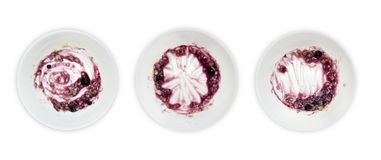A set of white plates with porridge and blueberry jam leftovers isolated on white background. Messthetics aesthetic concept. A pho Stock Images