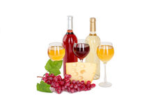 Set of white and rose wine bottles, glas and cheese, red and white grapes. Stock Photography