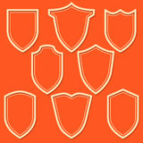 Set of white shield icons. Outline security signs on orange background. Stock Image