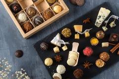 Set ?wietni czekoladowi cukierki i ser Bielu, ciemnej i dojnej czekolada, brie, b??kitny ser, ko?li parmisan na talerzu, ser, i zdjęcie stock