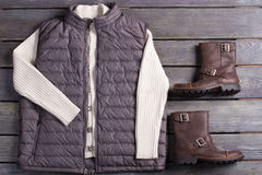 Set of winter menswear. Sweater, vest and boots on a wooden background Stock Photos