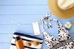 Set of woman`s accessories to beach season swimsuit, sunglasses, phone, sunscreen and hat with frangipani flower top view, flat la Stock Images