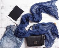 Set of woman`s items including scarf, tablet, handbag and jeans. Royalty Free Stock Photo