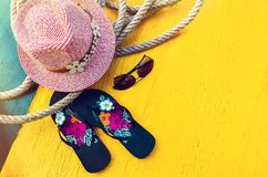 Set of Woman`s Things Accessories to Beach Season Straw Beach Woman`s Hat Yellow Background Flat Single. Copy space. Set of Woman`s Things Accessories to Beach Royalty Free Stock Images