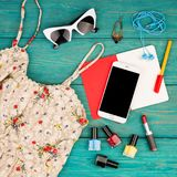 Set of woman stuff with dress, smart phone, notepad, accessory and nail polishes on blue wooden desk. Voyage concept - set of woman stuff with dress, smart phone stock photography