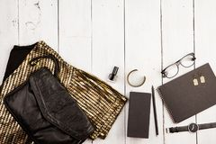 Set of woman stuff on white wooden desk: dress, bag, watch, glasses, notepad, accessories. Travel concept - set of woman stuff on white wooden desk: dress, bag royalty free stock photography