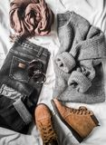 Set of women`s autumn, winter clothes on a light background - jeans, gray pullover oversize, suede brown boots and scarf. Fashion. Able clothes for walks, flat stock photos
