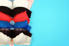 Set of women`s bra on blue background. Underwear fashion concept. Basic lingerie flatly top view