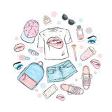 A set of women`s clothes. Teenage style. T-shirt with print in the form of lips, backpack, sneakers, watch, smartphone, cap, short Royalty Free Stock Image