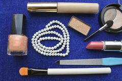 Set of women's cosmetics and pearl necklace on blue background. Royalty Free Stock Image