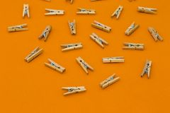 Set of wooden clothespins on bright background. Set of wooden clothespins on bright orange background Royalty Free Stock Photo