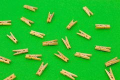 Set of wooden clothespins on green background. Set of wooden clothespins on bright green background Royalty Free Stock Photo
