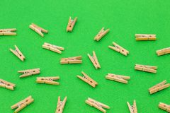 Set of wooden clothespins on green background. Set of wooden clothespins on bright green background Royalty Free Stock Photography