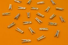 Set of wooden clothespins on orange background. Set of wooden clothespins on bright orange background royalty free stock images