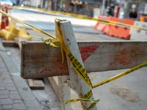 Wooden construction barriers sitting on street corner wrapped in yellow caution tape. Set of wooden construction barriers sitting on street corner wrapped in royalty free stock photography