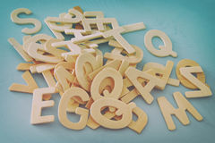 Set of a wooden letters of the English alphabet. On wooden blue background. Filtered image Royalty Free Stock Images