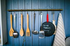 Set of wooden and metal kitchen utensils hanging on the blue wall stock images