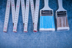 Set of wooden meter paintbrushes on scratched metallic backgroun Stock Images