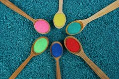 Set of wooden spoons with colored sand on blue stones royalty free stock image