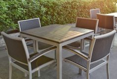 A set of wooden-steel table and rattan chairs on a roof deck floor beside a pool stock photos